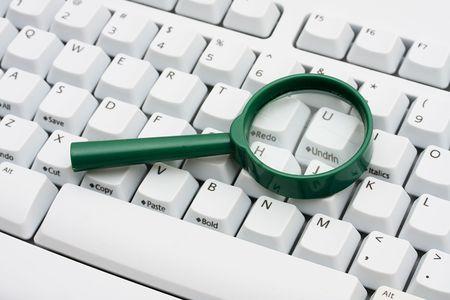 コンピューターのキーボードは、インターネット検索の上に座って拡大鏡