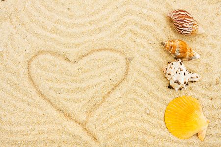 A seashell on sand with a heart drawn in it, beach background Stock Photo - 6529036