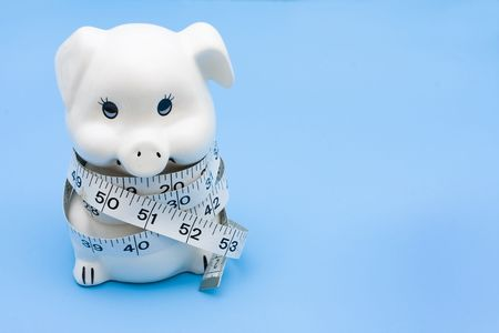 centimetres: A piggy bank with a measuring tape on a blue background, measuring your savings