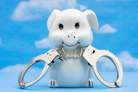 A piggy bank with handcuffs on a blue sky background, Protect your Savings Stock Photo - 6595058