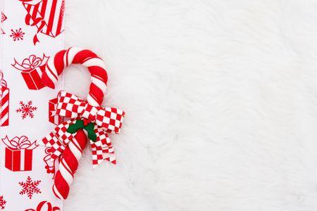 Een Suikergoed-riet met een rode huidige lint op een witte vacht achtergrond