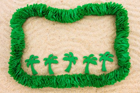 A green lei making a border on a sand background, Summer holiday border photo