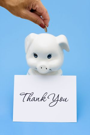 A piggy bank sitting with a thank you card on a blue background, thank you for saving photo