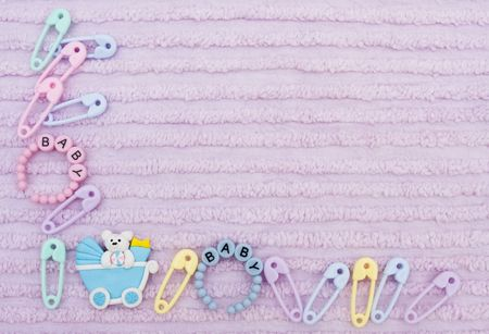 Diaper pins and a baby carriage on a lavender textured background, baby border photo