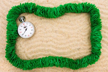 A green lei making a border on a sand background, Time to go on vacation photo
