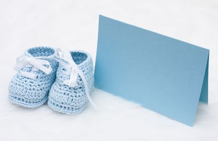 A pair of blue baby booties with a blank card on a white background, Message to the new baby 版權商用圖片