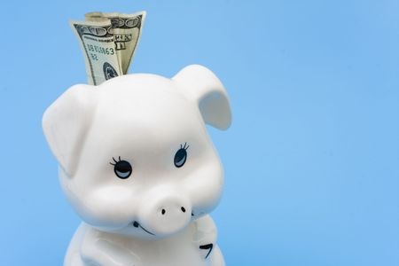 A piggy bank with cash in it on a blue background, Adding to your Savings photo