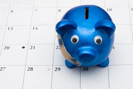 year financial statements: A blue piggy bank with adhesive bandage on a calendar, Are you hurting paying your bills