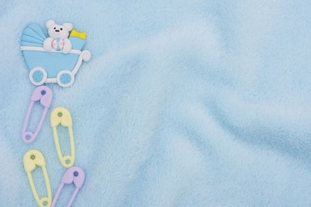 Diaper pins and a baby carriage on a blue textured background, baby border photo