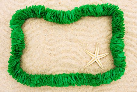 A green lei making a border on a sand background, Summer fun holiday border photo