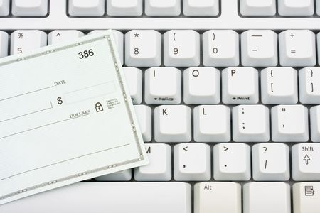 A blank cheque sitting on a computer keyboard, making money online