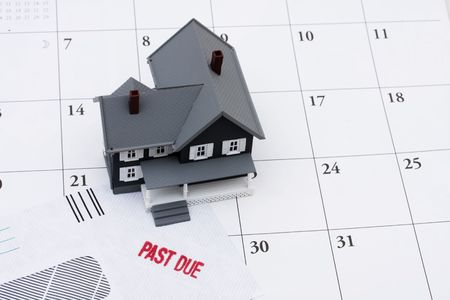 owe: A past due bill sitting with a model house on a calendar, Behind on your mortgage payments