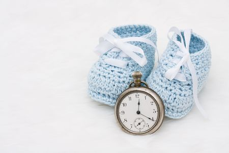 due date: A pair of baby booties with a watch on a white background, Babys Due Date