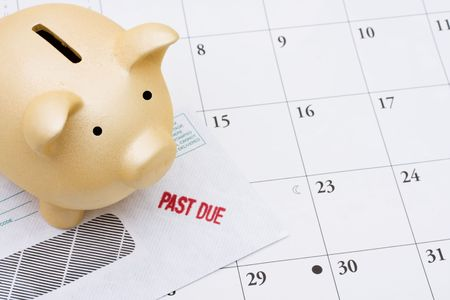 A past due bill sitting with a piggy bank on a calendar, Behind on your bills