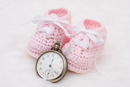 A pair of baby booties with a watch on a white background, Babys Due Date