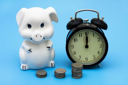 A piggy bank with coins and an old fashioned clock on a blue background, Compound Interest Stock Photo - 6773742