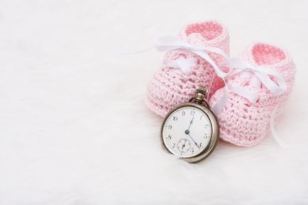 due: A pair of baby booties with a watch on a white background, Babys Due Date