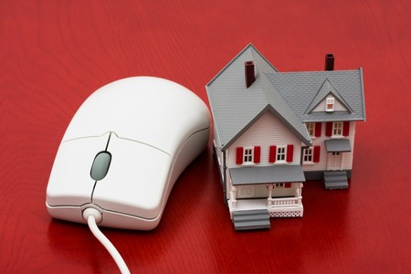 A model house sitting with a computer mouse on a red background, online real estate photo