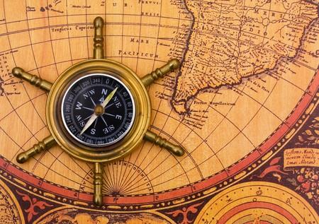 Een kompas op een oude achtergrond van de wereldkaart