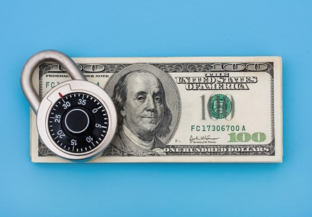 securing: A stack of one hundred dollar bills with a combination lock on it sitting on a blue background, securing finances Stock Photo