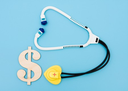 A toy stethoscope with a dollar sign on a blue background, medical costs Stock Photo - 6866728
