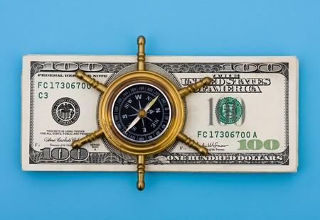 Une pile de billets de cent dollars avec une boussole dessus assis sur un fond bleu, explorer vos options financières  Banque d'images - 6894634