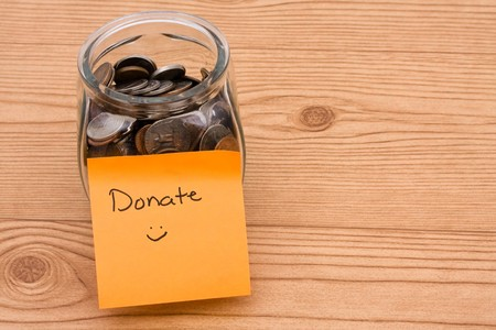 donates: A jar full of change sitting on a wooden background, Please help by donating money Stock Photo