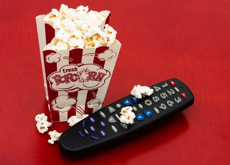 television remotes: A red and white container of popcorn on a wood background, Home entertainment