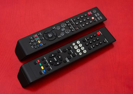 Two black remotes on a wooden background, remote controls