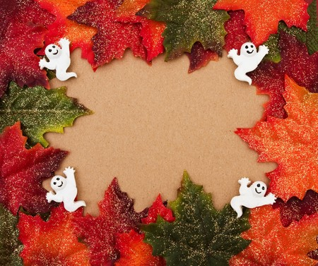 Fall leaves making a border on a beige background, Happy Halloween  photo