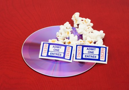 A few kernels of popcorn with a dvd and tickets on a wood background, movie and popcorn