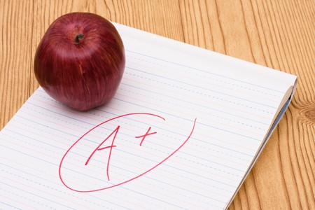 An apple on a piece of paper with a grade on it, good grades