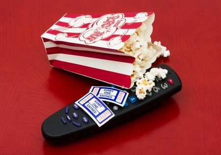 tv remotes: A red and white container of popcorn on a wood background, Home entertainment