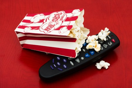 A red and white container of popcorn on a wood background, Home entertainment