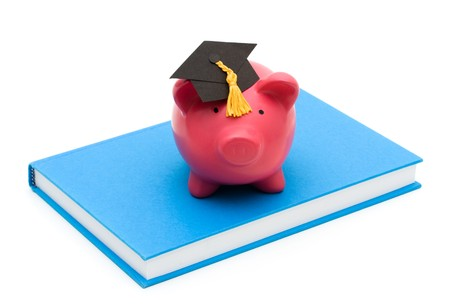 Piggy bank with graduation cap on a book isolated on a white background, education savings photo