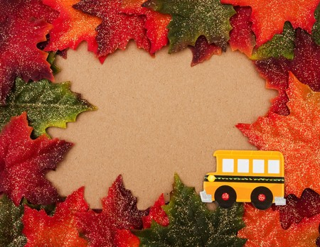 Fall leaves making a border on a beige background, Back to school photo