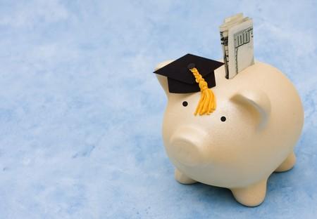 Piggy bank met afstuderen dop op een blauwe achtergrond, spaar geld voor studie