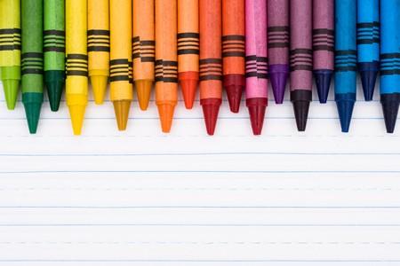 Kleurrijke krijt op een vel gelinieerd papier, onderwijs achtergrond