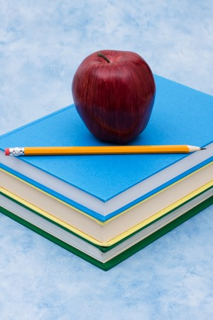 A stack of book with an apple and a pencil on a blue background, education photo