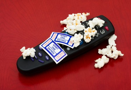 Popcorn and tickets with a remote control on a wood background, Home entertainment Stock Photo