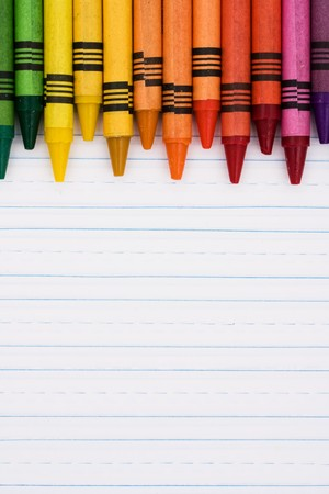 pastelky: Colorful crayons on a sheet of lined paper, Education background