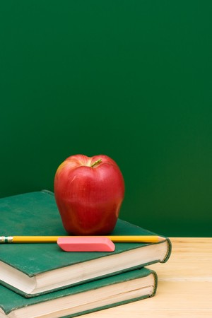 Two old books with an apple in front of the chalkboard, School Days Stock Photo - 7312539