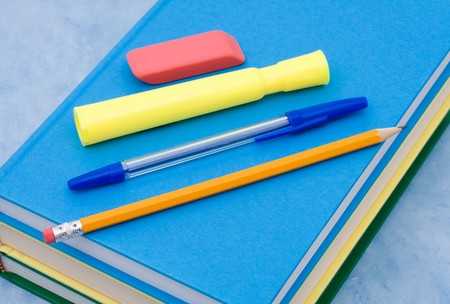 eraser mark: A stack of book with a pen, pencil, eraser and highlighter on a blue background, School Supplies Stock Photo