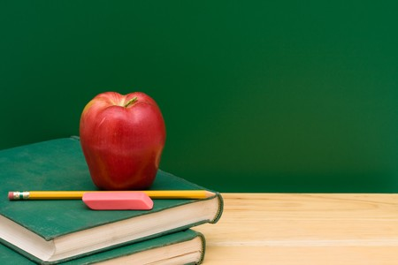 Two old books with an apple in front of the chalkboard, School Days