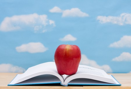 Open book with apple on table in front of sky, School Days