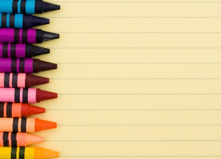 lined: Colorful crayons on a sheet of lined paper, Education background