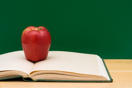 Open book with an apple in front of the chalkboard, School Days photo