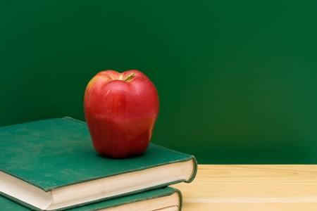 Two old books with an apple in front of the chalkboard, School Days photo