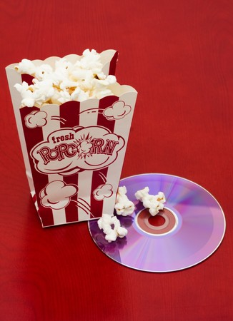 A bag of popcorn with a dvd and tickets on a wood background, movie and popcorn