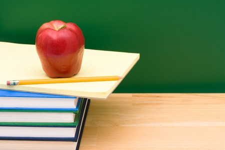 Stack of  books with an apple in front of the chalkboard, School Days photo